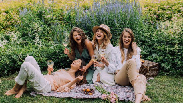 women sitting on green grass field