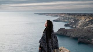 a woman wearing a shawl standing on a cliff